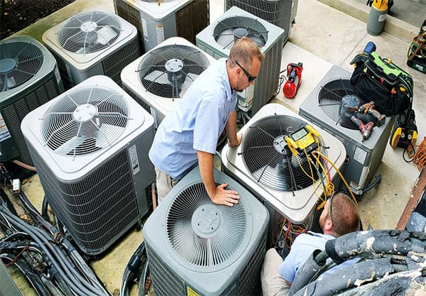 Two people working on air conditioning units -- best ac unit brand -- hvac careers