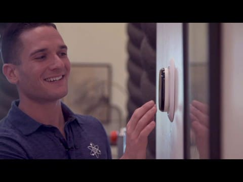 Technician adjusting thermostat -- choose our Tucson HVAC